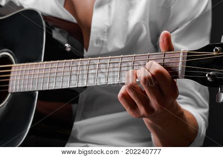 A close-up picture of a man's hands playing a guitar pop or rock music on a saturated black background. A male in a white blouse practicing in playing guitar. Enjoying carefree time.