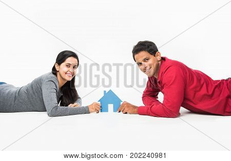 stock photo showing side angle of Indian or asian smart and cheerful / happy couple holding 3D paper house model and lying isolated over white background, asian couple and real estate concept.
