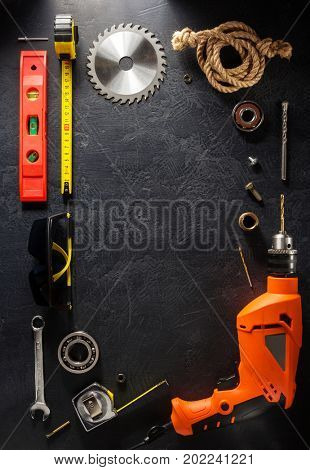 electric drill and tools on black background