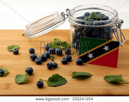 Saint Kitts And Nevis Flag On A Wooden Plank With Blueberries Isolated On White