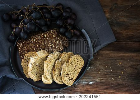 Dark and light wholemeal bread with seeds and blue grapes on a rustic wooden table top view from above generous copy space
