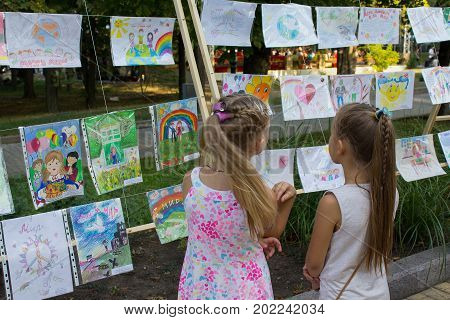 Donetsk Ukraine - August 27 2017: Children visiting the exhibition of children's drawings at the exhibition in the park named Sherbakova during the celebration of the city's day