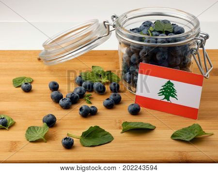 Lebanese Flag On A Wooden Plank With Blueberries Isolated On White