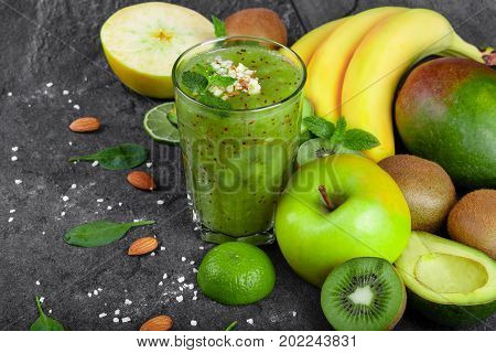A top view of a colorful composition of a kiwi smoothie with grated almond and tropical fruits on a dark stones background. Whole and cut apples, kiwi, avocado and a branch of bananas on a table.