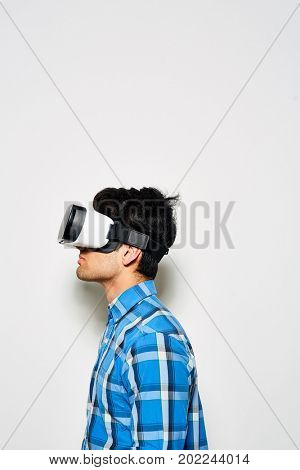 Concentrated young man in buttoned-up checked shirt using VR headset while standing against white background, profile view