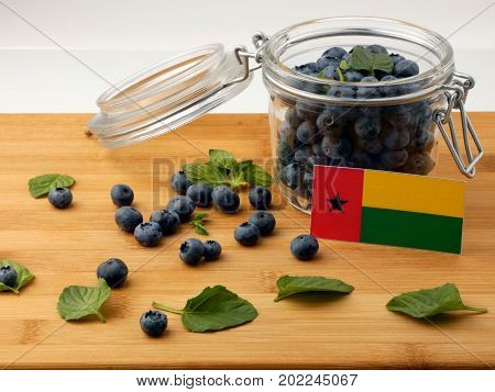 Guinea Bissau Flag On A Wooden Plank With Blueberries Isolated On White