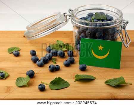Mauritania Flag On A Wooden Plank With Blueberries Isolated On White