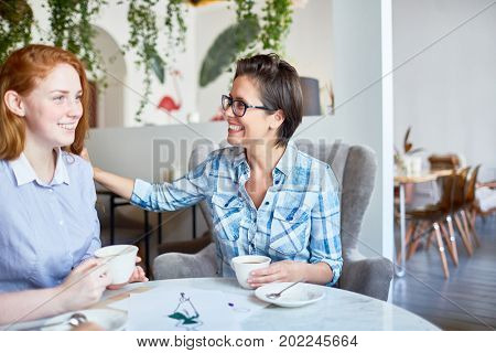 Happy employer lauding happy young subordinate by cup of coffee in cafe