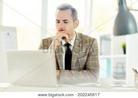 Business leader or stock-broker sitting by workplace in front of laptop in office