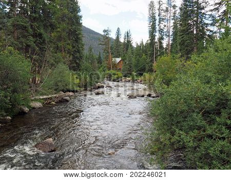 A small creek or stream runs through a forest area near Grand Lake in Colorado. The stream is surrounded by trees and a log cabin home. In the background are the Rocky Mountains.