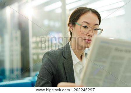 Corporate worker reading latest financial news in newspaper