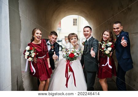 Wedding Couple And Groomsmen With Bridesmaids Posing Next To The Old Building's Walls.