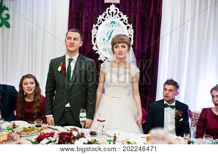 Awesome Wedding Couple Standing At Their Table With Bridesmaids And Groomsmen Sitting Beside.