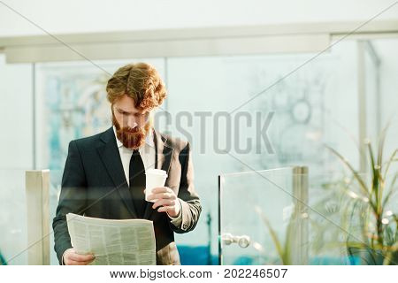 Serious economist or banker with drink reading morning news in office