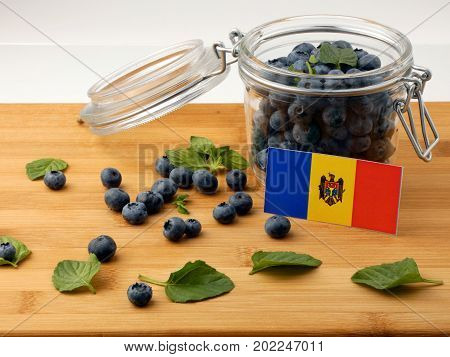 Moldovan Flag On A Wooden Plank With Blueberries Isolated On White