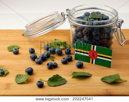 Dominica Flag On A Wooden Plank With Blueberries Isolated On White