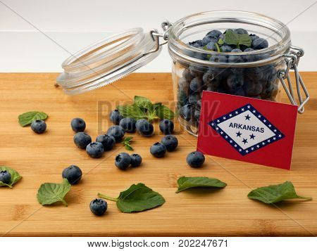 Arkansas Flag On A Wooden Plank With Blueberries Isolated On White