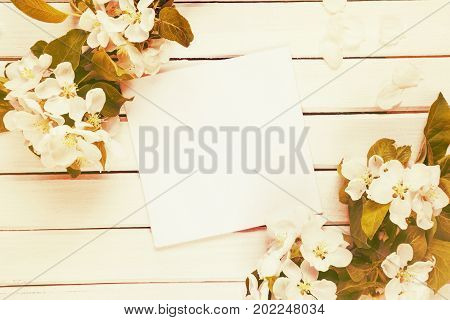 Scrapbook page of wedding or family photo album with copy-space frame with white flowers and green leaves on light wooden background; top view flat lay overhead view. Toned image. Mocap