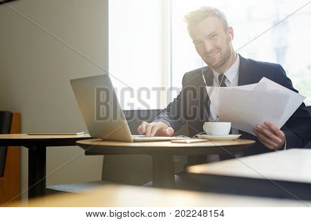 Successful young economist with documents working by cup of tea