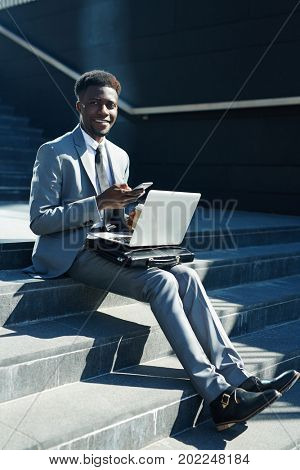 E-businessman with gadgets sitting on street staircase and networking