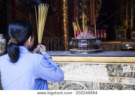 Ho Chi Minh City, Vietnam - March 26, 2017: Woman praying in Ong Bon Pagoda, dedicated to Ong Bon, the guardian who presides over happiness and wealth, in Cholon, the Chinatown area of Saigon