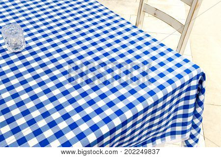 Empty Table Covered With Blue And White Chequered Tablecloth Next To White Wooden Chair.