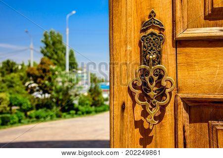 Golden carved handle of the wooden door at sunny summer day in Hazrat Imam Ensemble in the center of Tashkent city, Uzbekistan