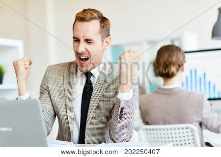 Bearded young trader doing winner gesture while looking at computer screen, interior of open plan office on background