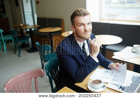 Young economist working with papers while sitting in cafe