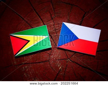 Guyana Flag With Czech Flag On A Tree Stump Isolated
