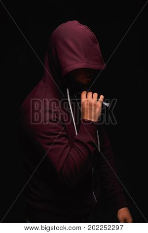 A photo of a desperate young drug addict is wearing a hood on a saturated black background. A hopeless addict male with a syringe in his hand. An addict injects a narcotic substance into the neck.