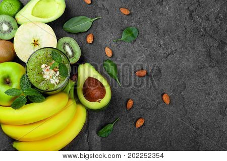 A view from above of a refreshing and exotic smoothie full of vitamins and kiwis on a gray table background. A composition from ripe bananas, organic avocado, cut kiwi and apple on a desk. Copy space.