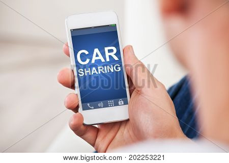 Closeup of man's hand holding smart phone with car sharing app on screen at home