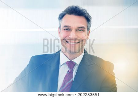 Portrait of mature businessman in suit smiling in office