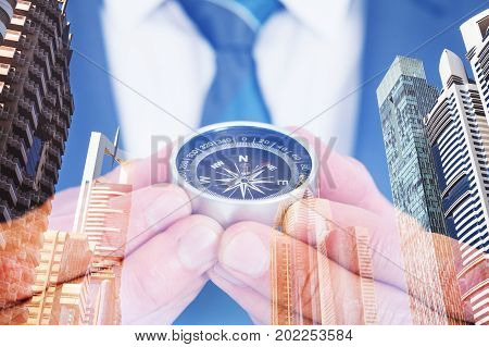 Double exposure of businessman holding navigational compass over city background