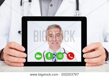 Midsection of male doctor having conference call with superior on digital tablet in hospital