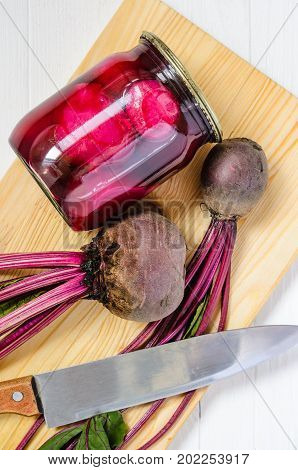 Glass jar with canned beets home made and fresh organic beets with haulm with cutting board and big knife on a white wooden background top view. Beets on kitchen table background