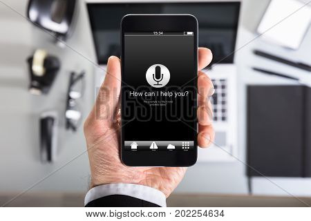 How can I help you? text on smart phone screen held by businessman in office