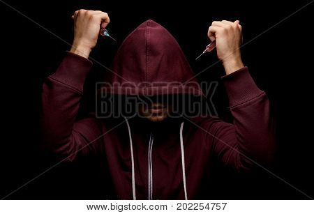 An addict male with syringes full of red liquid drugs in his hands on a saturated black background. A hopeless drug addict is going through addiction crisis. Depression, abuse, fear concept.