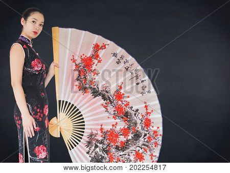 Digital composite of Geisha and giant fan against navy chalkboard