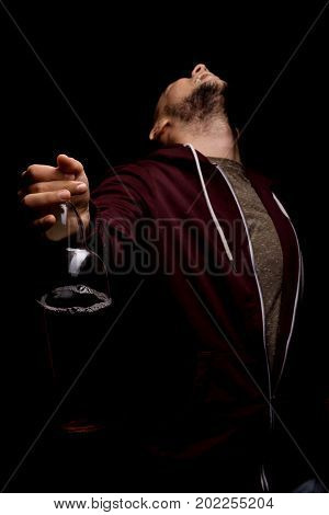 A fun man wearing a dark red hood is holding a big bottle of alcoholic drink on a saturated black background. An addicted, depressed, stressed and problematic male with alcoholic intoxication.