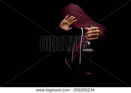 The man in the hood refused to drink alcohol and showed a sign of the stop sign on a saturated black background. A young male saying no more to alcohol with his body language.