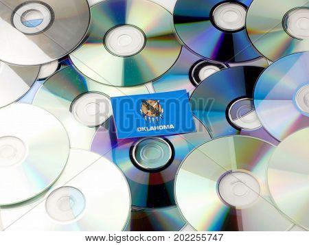 Oklahoma Flag On Top Of Cd And Dvd Pile Isolated On White