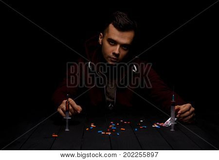 A man wearing dark red clothes sitting at a table with a lot of colorful narcotics and syringes with heroin on a saturated black background. A young guy is abusing drugs. Depression and abuse concept.