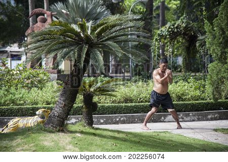 Ho Chi Minh City, Vietnam - March 27, 2017: Vietnamese man practice Tai Chi early in the morning at Tao Dan park in Ho Chi Minh city, Saigon,