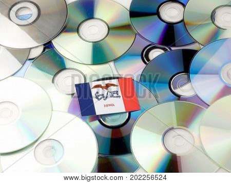Iowa Flag On Top Of Cd And Dvd Pile Isolated On White
