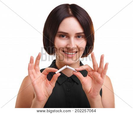 A cheerful and confident woman holding a broken nicotine cigarette isolated over the white background. A modern girl with a short haircut is against unhealthy smoking. Health awareness concept.