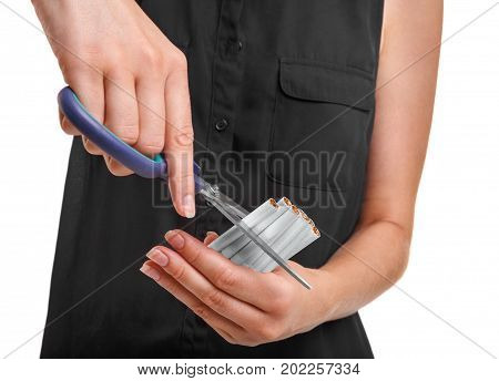Close-up picture of female's hands cutting a bunch of unhealthy nicotine or tobacco cigarettes with colorful scissors isolated over the white background. Health, care, wellbeing concept.