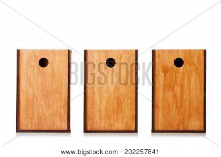 A group of three old light brown wooden boxes organized isolated over the white background. Closed boxes for storage, packaging, delivery or shipping. Wooden crates for keeping toys. Copy space.