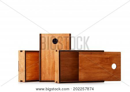 Close-up picture of classic opened, closed and unpacked wooden boxes isolated over the white background. Vintage, rustic, antique containers made of natural wooden material. Copy space.
